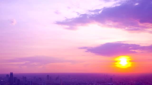 vídeos de stock, filmes e b-roll de lapso de tempo do sol contra a paisagem urbana - crepúsculo