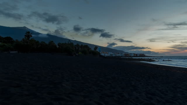 4K Sunset Time lapse (panning right) at the beach in Puerto de la Cruz with El Teide, Tenerife, Spain