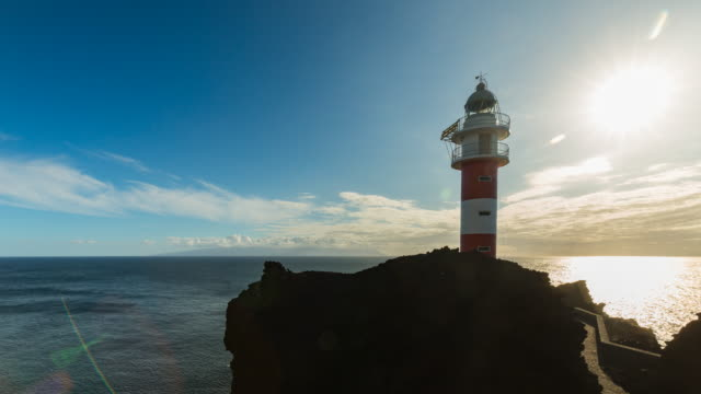 4k sunset time lapse at the historic teno lighthouse, tenerife north, spain, with the view of another island in the background - atlantic ocean stock videos & royalty-free footage