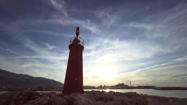 vídeos de stock e filmes b-roll de sunset time lapse from denia´s seaport - farol estrutura construída