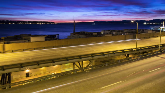 A sunset time lapse of traffic on the Viaduct in Seattle, showcasing Elliott Bay, with sporadic boat traffic.