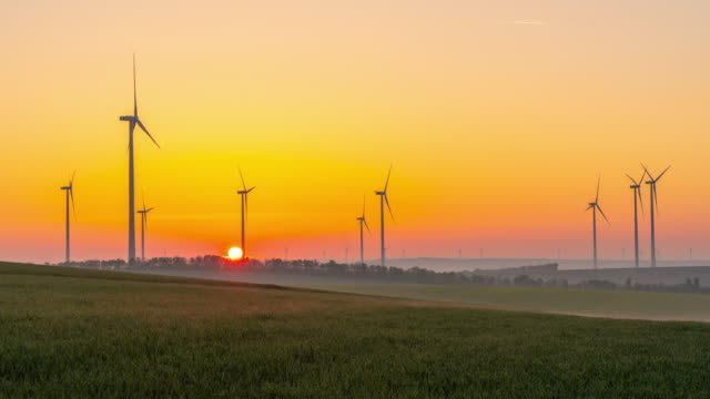 t/l time warp sunset time lapse shot of wind turbines spinning in the countryside - fast motion stock videos & royalty-free footage