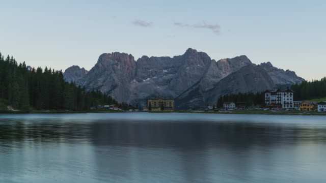 t/l sunset timelapse of lake misurina / lago di misurina and the rehabilitation center in front of the beautiful mountain scenery in the dolomites, italy - sonnenuntergang stock videos & royalty-free footage