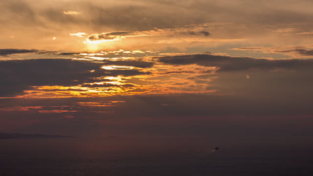 Sunset timelapse over the sea with a ship leaving