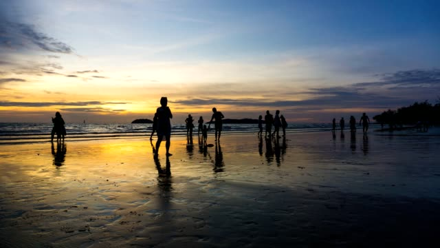Sunset to night timelapse of Tanjung Aru Beach with people silhouettes
