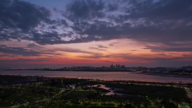 sunset to night view of baegot life park and songdo international business district / yeonsu-gu, incheon, south korea - purple stock-videos und b-roll-filmmaterial