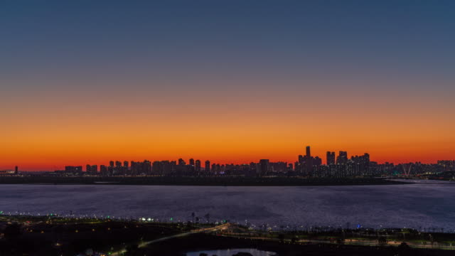 sunset to night view of baegot life park and songdo international business district / yeonsu-gu, incheon, south korea - orange color stock videos & royalty-free footage
