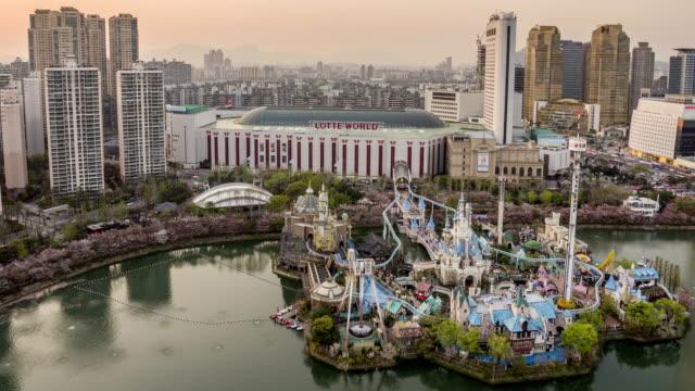 sunset to night view of lotteworld amusement park on seokchonhosu lake with cherry blossoms - sunset to night stock videos & royalty-free footage