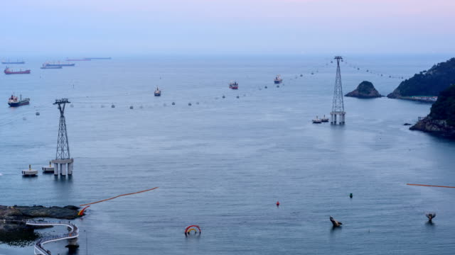 sunset to night view of overhead cable car, sailing tourboats and seascape of songdo beach (famous travel destinations) - sunset to night stock videos & royalty-free footage
