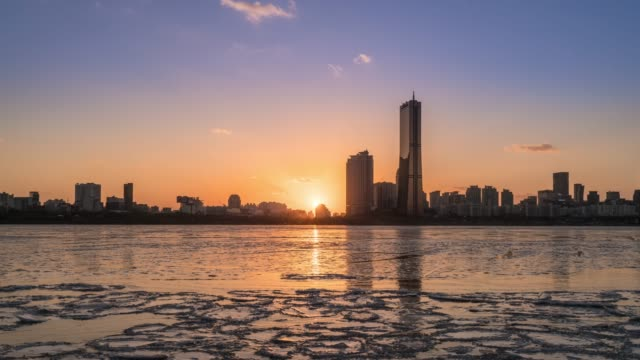 sunset to night view of the frozen han river and city buildings in yeouido district, seoul at winter - complexity stock videos & royalty-free footage