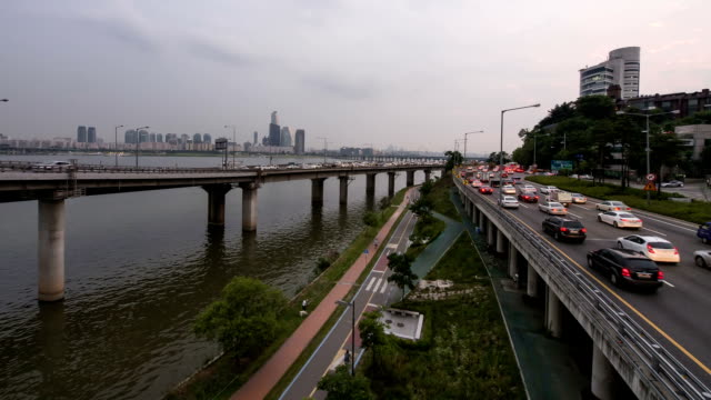 sunset to night view of traffic moving on gangbyeonbungno(riverside expressway)  and the han river near yeouido business district - sunset to night stock videos & royalty-free footage