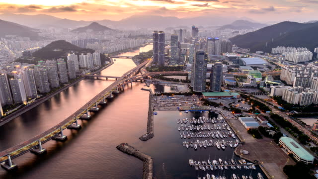 Sunset to night view of traffic moving on the bridges, cityscape of Centum City (Busan Marine City) and the anchored yachts in Yachting Center