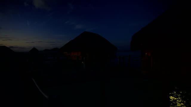 sunset tropical lagoon with overwater bungalows bora bora - polynesian ethnicity stock videos & royalty-free footage