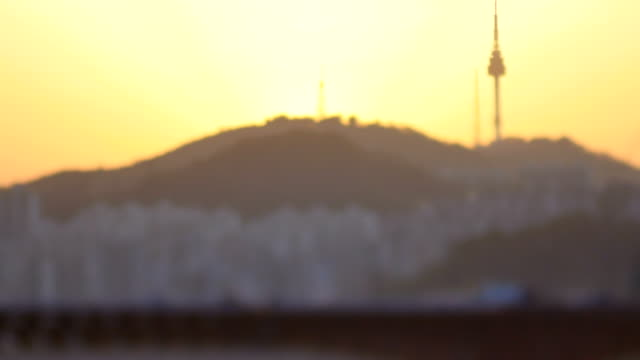 Sunset view cars on the bridge and N Seoul Tower behind it (tourist attraction)