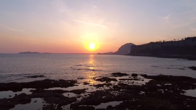 sunset view of baksugijeong cliff and sea / seogwipo-si, jeju-do, south korea - cliff video stock e b–roll
