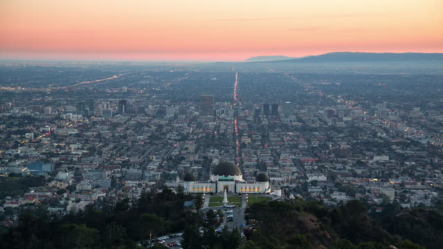 sunset view of griffith park observatory over a sprawling los angeles - griffith observatory stock videos & royalty-free footage