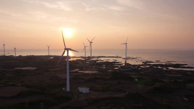 sunset view of many wind turbines at coastal feature - coastal feature stock-videos und b-roll-filmmaterial