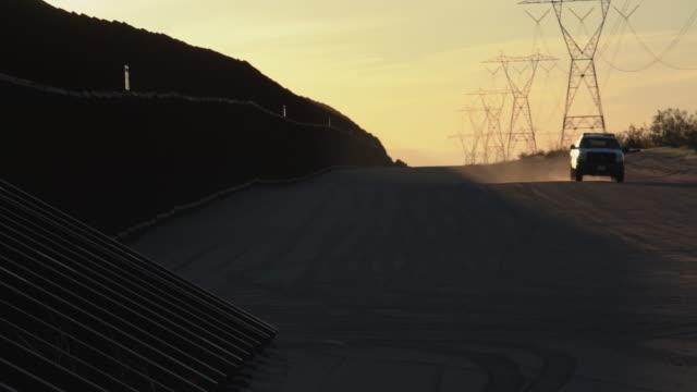 vídeos y material grabado en eventos de stock de una vista de la puesta del sol de la muralla fronteriza internacional, un agente que patrulla, california, lado de los estados unidos - prejuicio