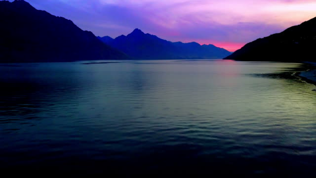 Sunset views over the Queenstown's Lake Wakatipu. The majestic Remarkables mountain range looms in the background.