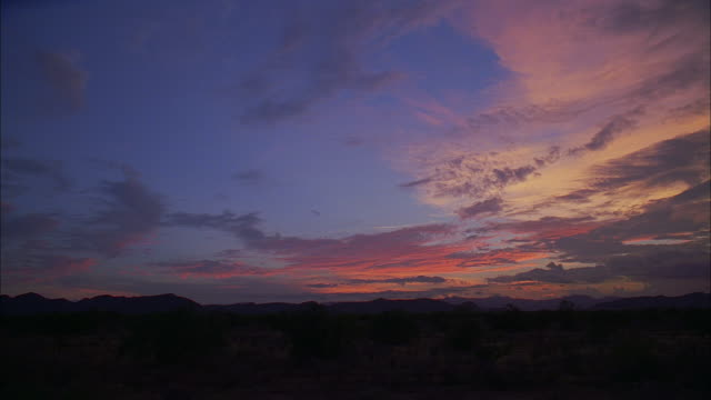 vidéos et rushes de la sunset with blue and purple sky, clouds, and a flash of fiery red - violet