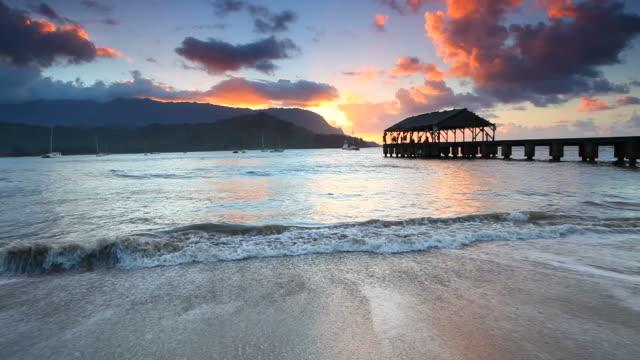 sunset with hanalei pier, kauai, hawaii - kauai stock videos & royalty-free footage