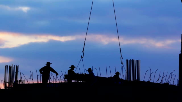 Sunset with Silhouettes of  Workers in Construction Site