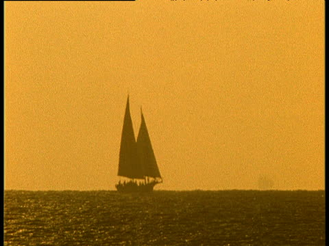 sunset, yellow sky, silhouette of boat as it sails across shot - eskapismus stock-videos und b-roll-filmmaterial