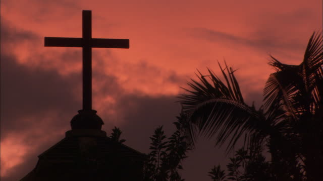Sunsets behind silhouetted cross on top of church Available in HD.