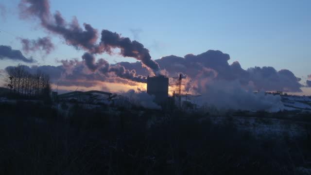 sunset-smoke rising from pulp factory - dämmerung stock-videos und b-roll-filmmaterial