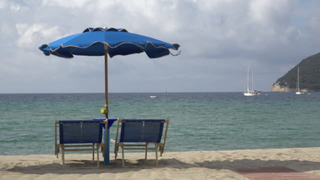 sunshade and deck chairs on beach - beach umbrella stock videos and b-roll footage