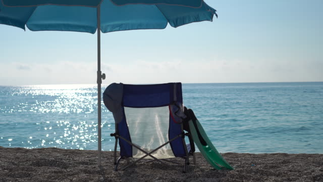 sunshade and sunbed on the beach at sunset - deck chair stock videos & royalty-free footage