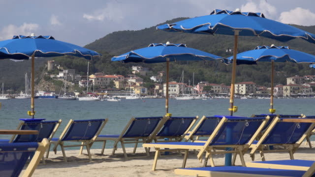 vídeos de stock, filmes e b-roll de sunshades and deck chairs on beach of marina di campo - ancorado