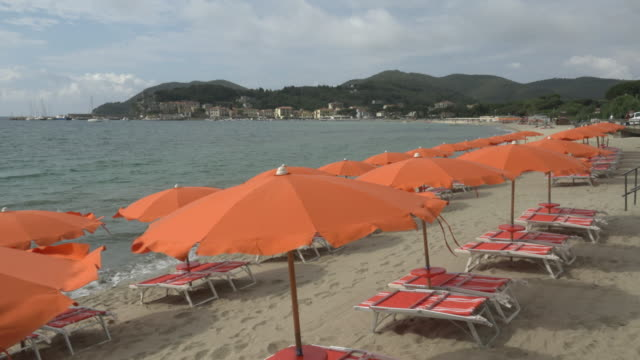 sunshades and deck chairs on beach of marina di campo - island of elba stock videos & royalty-free footage