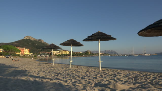 pan / sunshades on beach of golfo aranci - sassari stock videos & royalty-free footage