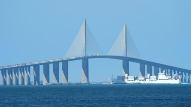 sunshine bridge and cargo boat - zement stock-videos und b-roll-filmmaterial