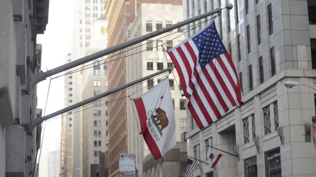 Sunshine lights hits the California State flag and America flag blow in the wind in San Francisco US on December 17 2013 California State Flag on...
