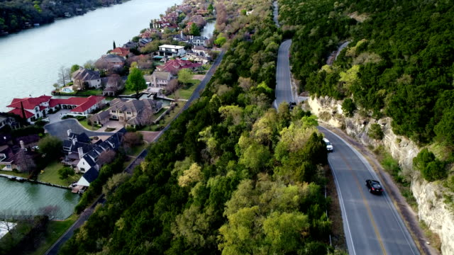 Sunshine on the Curvy cliff side road on Mount Bonnell in Austin , Texas , USA with mansions down below next to the Lake