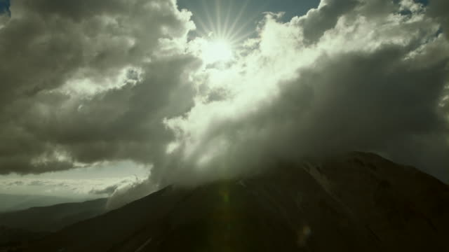 sunshine pierces the cloudcover over mount lassen in lassen volcanic national park. - separation stock videos & royalty-free footage