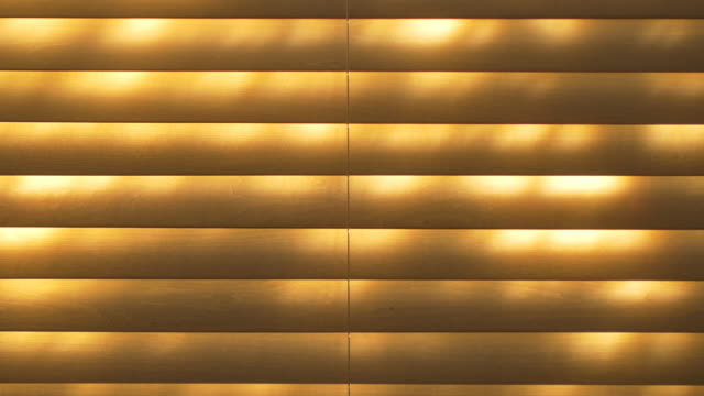 sunshine plays upon wooden venetian blinds. - blinds stock videos & royalty-free footage