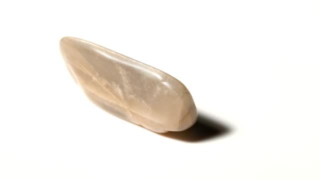 vídeos de stock e filmes b-roll de sunstone mineral stone sample in rotation with white background - jaspe mineral