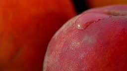 Super close up of the red peach surface with a drop of water