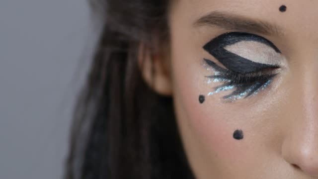 Super close-up of fashion`s model eye in a stage make-up blinking. Fashion video.