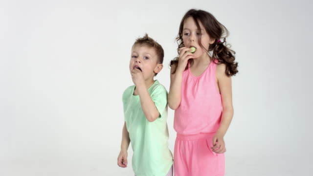 super cute brother and sister eating cucumber - slowly rotating on turntable - スタジオ撮影点の映像素材/bロール