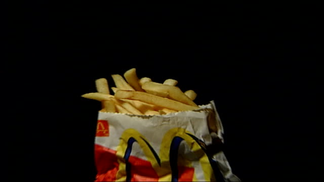 stockvideo's en b-roll-footage met 'super size me' film criticises mcdonalds food itn london mcdonald's chips in paper bag pull out larger portion sizes appearing ext burger held by... - verschijning