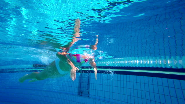 HD Super Slo-Mo Underwater: Young Woman Swimming Breast stroke