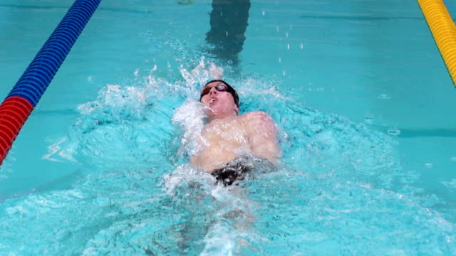 HD Super Slo-Mo: Young Male Swimmer at Backstroke