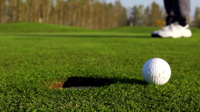 hd super slo-mo:shot of golfball missing the hole - golf shoe stock videos & royalty-free footage