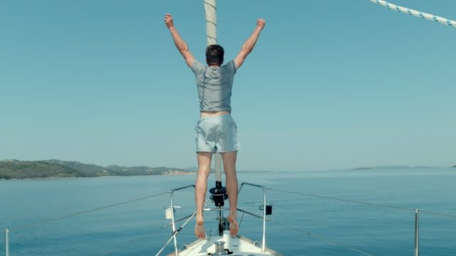ms super slow motion carefree man jumping on sailboat - boat point of view stock videos & royalty-free footage