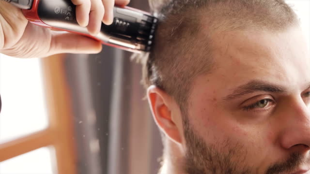 super slow motion close up shot of man preparing for army getting his hair cut - raso video stock e b–roll
