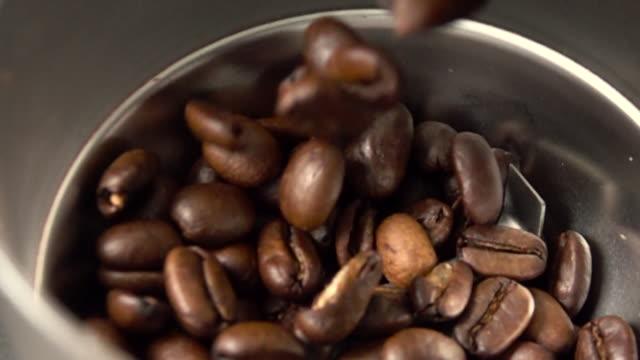 vídeos y material grabado en eventos de stock de cámara súper lenta ? los granos de café se vierten en un molinillo de café - secuencia sin editar